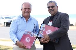 Two men smiling holding RQI folders